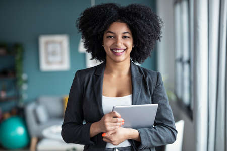 Portrait of smart afro young entrepreneur woman using her digital tablet while standing looking at camera in the office at home.