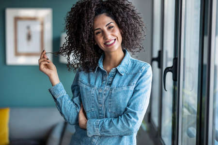 Portrait of smart beautiful young businesswoman smiling while looking at camera standing in living room at home.