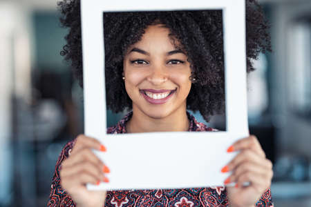 Shot of beautiful afro business woman holding hands frame while posing to camera to snapshot in the office at home. Foto de archivo