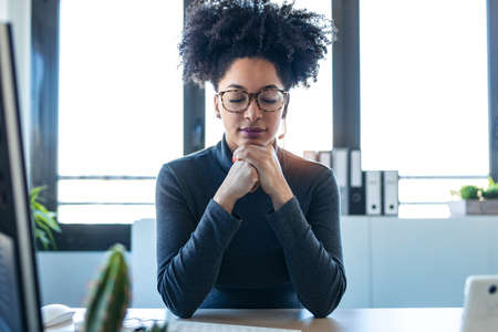Portrait of beautiful afro business woman relaxing while closing eyes and thinking in the office.