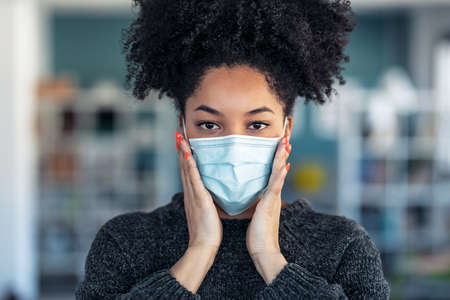 Portrait of young beautiful afro woman putting on an hygienic mask to prevent others from a virus while looking at camera in the home.