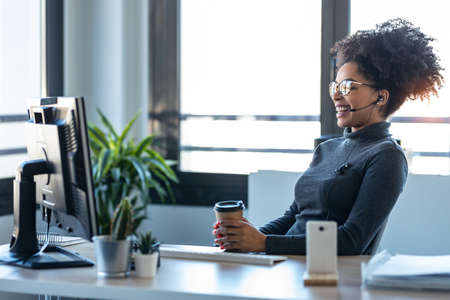 Shot of beautiful young afro business woman making video call with computer while talking with earphone sitting in the office.