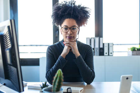 Portrait of beautiful afro business woman relaxing while looking at camera in the office.