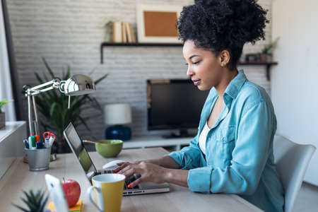 Shot of beautiful young afro business woman working with laptop sitting in the office at home.
