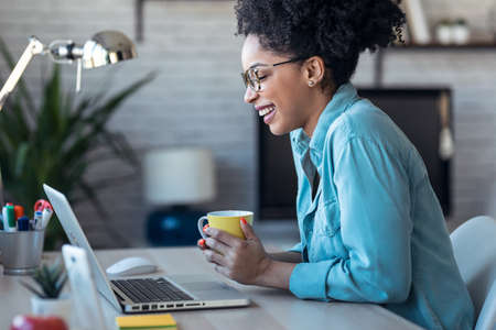 Shot of beautiful young afro business woman making video call with laptop while drinking coffee sitting in the office at home.