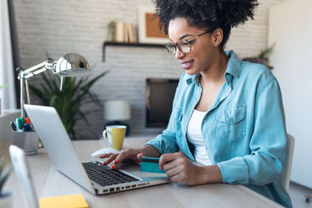 Shot of pretty young afro woman shopping online with credit card with laptop while working on office at home.