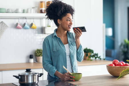 Shot of smiling young afro woman sending an audio with her mobile phone while eating noodles with chopsticks in the kitchen at home.