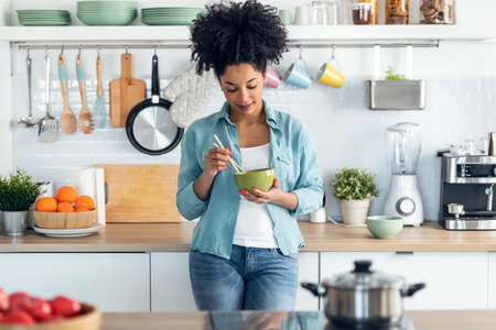 Shot of beautiful afro woman eating noodles with chopsticks while standing in the kitchen at home.