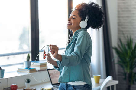 Shot of motivated young afro woman listening to music with headphone while dancing in living room at home.