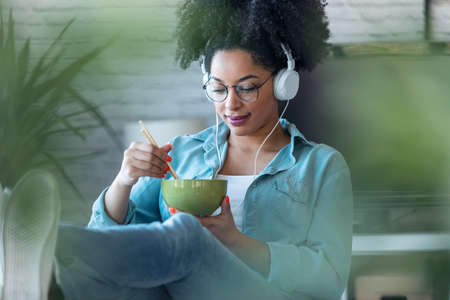 Shot of beautiful afro woman eating noodles with chopsticks while listening music with headphone of work sitting on chair at office at home.