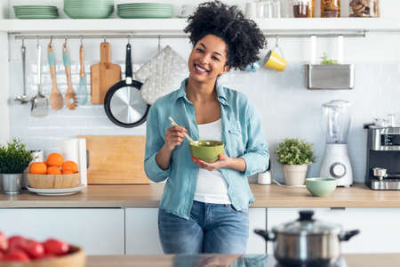 Shot of beautiful afro woman eating noodles with chopsticks while looking at camera standing in the kitchen at home. Foto de archivo