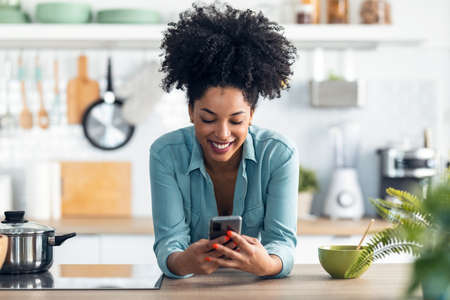 Shot of beautiful afro woman sending messages with her smartphone while eating noodles with chopsticks in the kitchen at home.