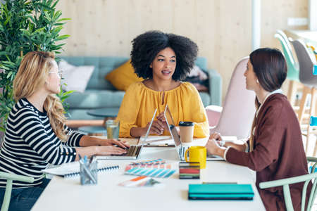 Shot of casual multiethnic business women working with laptops while talking of they new projects together in coworking place.