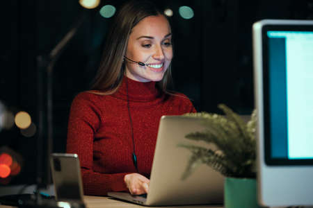 Shot of beautiful smiling young business woman working with computer while talking with earphone sitting in the office at night.