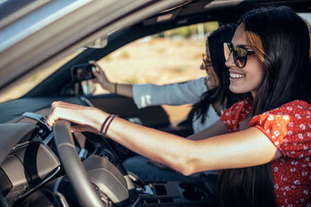 Shot of pretty young women taking a photo while driving a car on road trip on beautiful summer day.