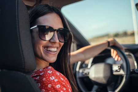 Portrait of beautiful young woman driving a car while smiling to the camera. Stock fotó