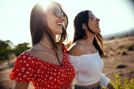 Shot of two smiling young women talking anad laughing while enjoying summer on road trip. Stock fotó