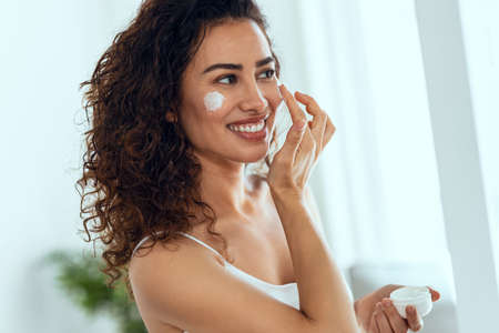 Portrait of beautiful young woman caring of her skin while putting on cream looking at mirror at home. Stock fotó