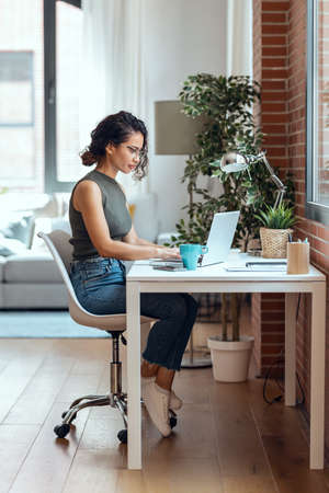 Shot of concentrated business woman working with laptop in living room at home. Stock fotó
