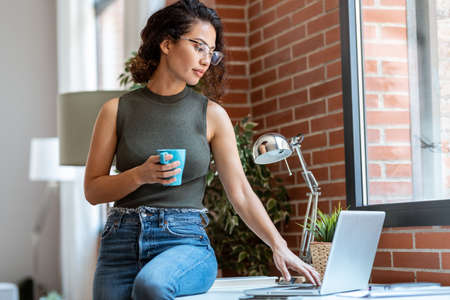Shot of beautiful business woman working with laptop while drinking coffee in living room at home. Stock fotó