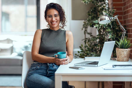 Shot of smiling business woman working with laptop while drinking coffee looking at camera in living room at home.