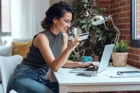 Shot of cute woman holding white credit card for shopping online with computer while sitting in living room at home.