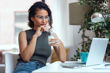 Shot of beautiful young business woman working with laptop while eating yogurt in living room at home.
