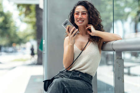 Shot of smiling young business woman using her mobile phone sitting on a bench in the street.