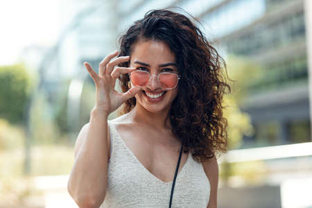 Portrait of beautiful young woman smiling while looking at camera standing in the street. Stock fotó