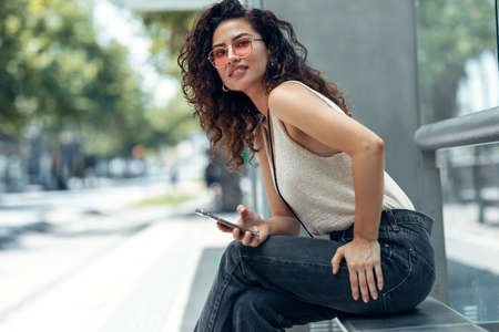 Shot of pretty young business woman using her mobile phone while waiting for someone sitting on a bench in the street. Stock fotó