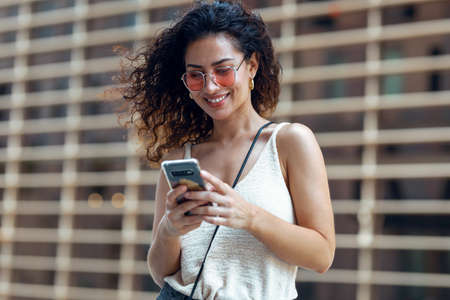 Shot of beautiful young business woman using her mobile phone while walking down the street.