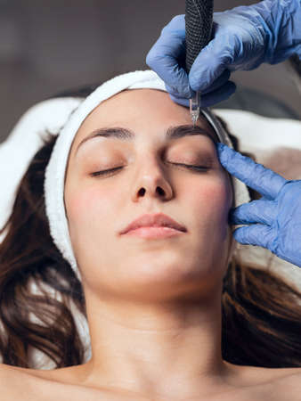 Shot of cosmetologist making micropigmentation injection on face for rejuvenation while lying on a stretcher in the spa center.