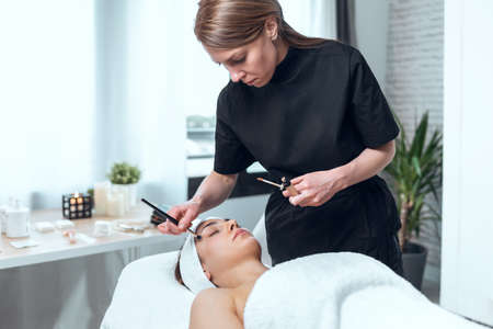 Shot of cosmetologist applying make-up to beautiful woman lying on a stretcher in the spa center.