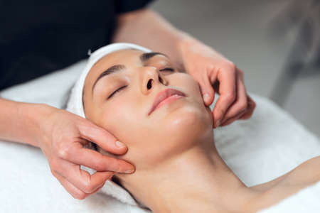 Shot of cosmetologist making face massage for rejuvenation to woman while lying on a stretcher in the spa center.
