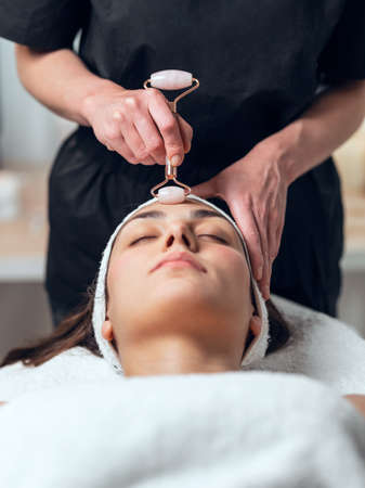 Shot of cosmetologist making face therapy for rejuvenation to woman while lying on a stretcher in the spa center.