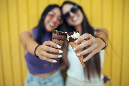 Shoot of two beautiful young women eating ice cream while having fun on yellow background.