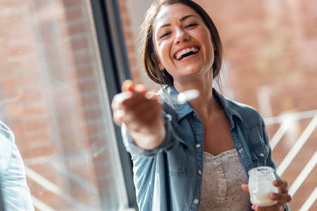 Portrait of beautiful smiling woman having fun while feeding yogurt to camera at home.