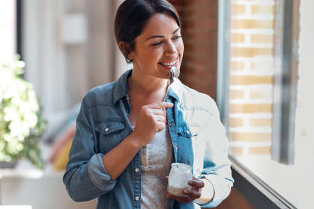 Shot of happy beautiful woman eating yogurt while standing in living room at home.