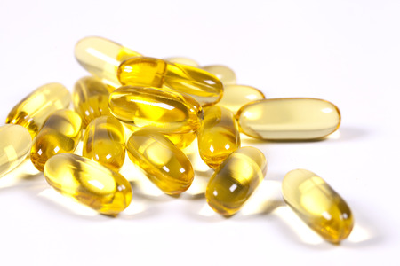 Vitamin E supplement capsules closeup on a white  photo