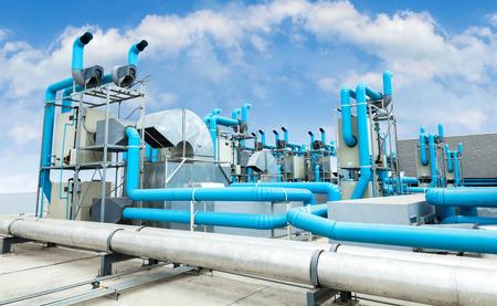 Industriële airconditioner op het dak met blauwe hemel