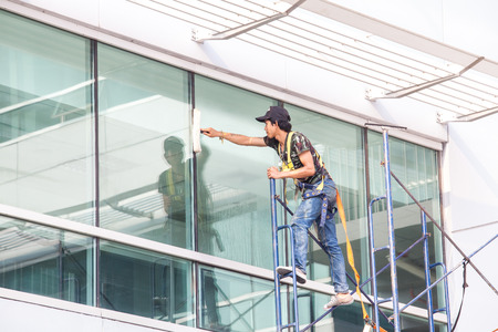 PATHUMTHANI THAILAND - MARCH 27, 2014  Unidentified workers washing the windows facade of a new build before the official opening on April 01, 2014 in National Science and Technology Development Agency, Thailand