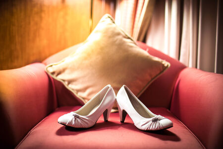 red sofa: Wedding Shoes waiting for the bride, on red sofa.