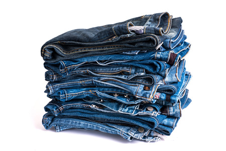 Lot of different blue jeans isolated on white background photo