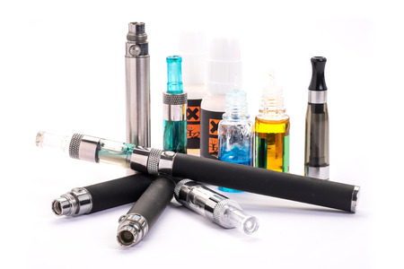 nicotine: Group of electronic cigarette nicotine inhalator ,bottles with liquids behind the inhalator. isolated on white background