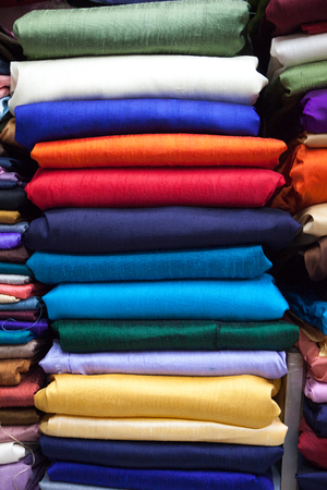 colorful fabric silk rolls the stacked in the shop