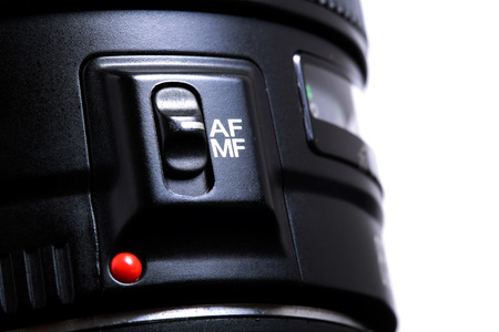 auto focus: Detail of the auto focus switch on a photo lenses isolated on white background Stock Photo