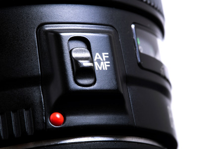Detail of the manual focus switch on a photo lenses isolated on white background