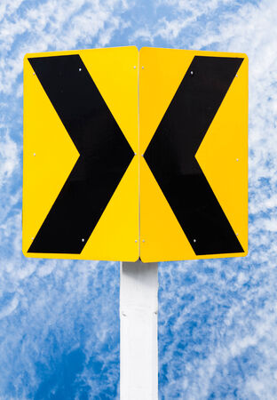 road signs indicating direction on curved road in blue sky background photo