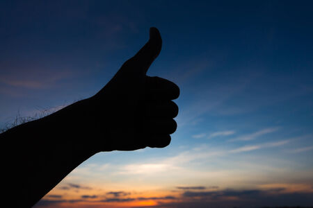 Thumbs up hand silhouette in sky photo