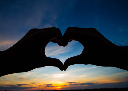 Love shape hand silhouette in sky photo